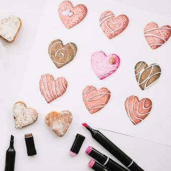 Geschilderde harten op papier in de buurt van markeringen en cookies