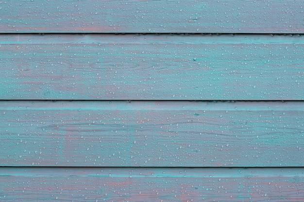 Geschilderde houten hekwerk achtergrond met regen waterdruppels, nat, veel contrast houten textuur, horizontaal