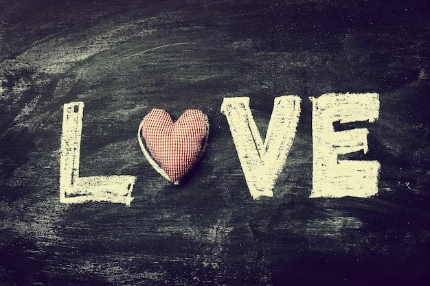 Geschilderde letters love met rood hart op oude houten bord bac
