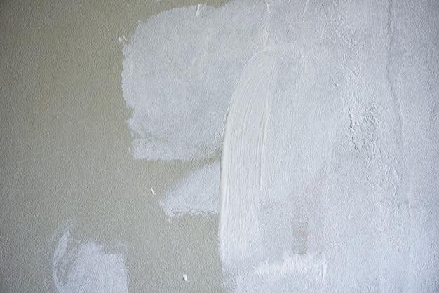 Geschilderde muurachtergrond, schilder die een huismuur schildert met een verfpoller
