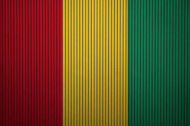 Geschilderde nationale vlag van guinee op een betonnen muur