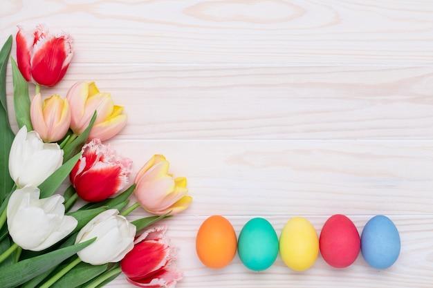 Geschilderde paaseieren en tulpen op een houten muur, bloemen feestelijk frame. lente, april.