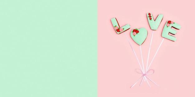 Geschilderde peperkoek in vorm van woordliefde als ballonnen verbonden door lint op roze