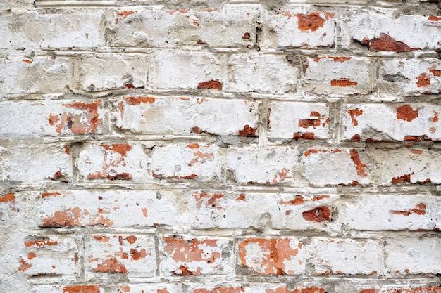 Geschilderde rode bricked muur die in wit wordt gekleurd.