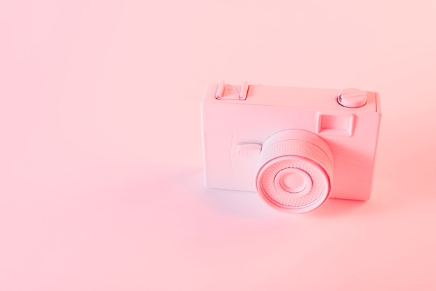 Geschilderde roze camera tegen roze achtergrond