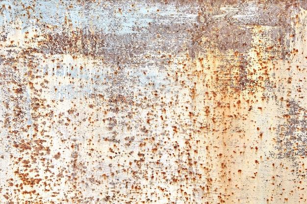 Geschilderde staalplaat met vervaagde en versleten beige verf, met vlekken van corrosie of roest, abstracte textuur voor.