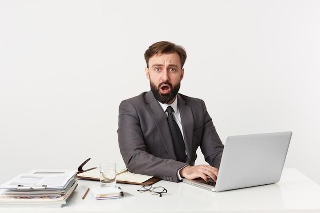 Geschokt aantrekkelijke bebaarde zakenman, topmanager zittend op het bureaublad in kantoor, camera kijken met wijd open mond, hoorde het schokkende nieuws. gekleed in een duur pak met stropdas.