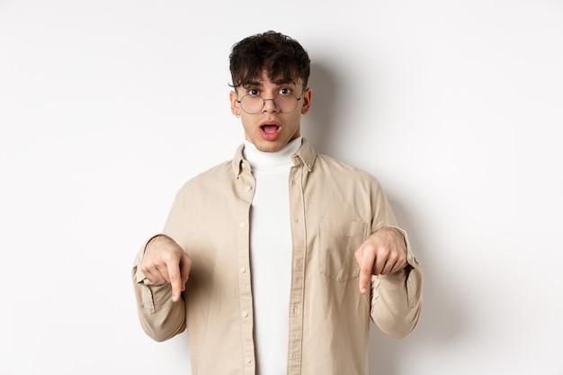 Geschokt aantrekkelijke jonge man die iets geweldigs laat zien, laat de kaak vallen en hijgt van ontzag, wijzende vingers naar beneden, staande op een witte achtergrond.