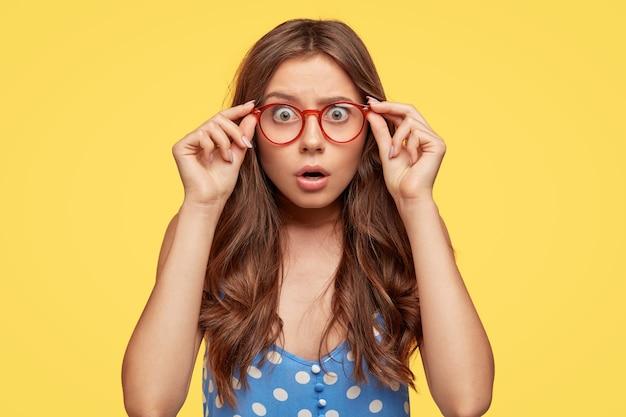 Geschokt aantrekkelijke jonge vrouw met bril poseren tegen de gele muur