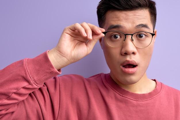 Geschokt aardig chinees mannetje in bril reageert emotioneel op iets met geopende mond
