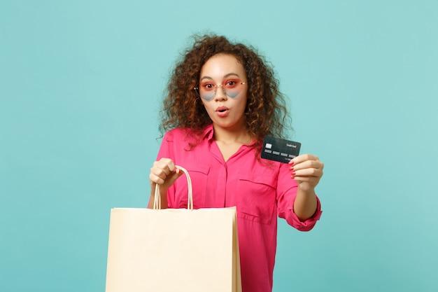 Geschokt afrikaans meisje in hartzonnebril houdt pakkettas met aankopen vast na het winkelen met creditcard geïsoleerd op blauwe turkooizen achtergrond. mensen oprechte emotie levensstijl concept. bespotten kopie ruimte.