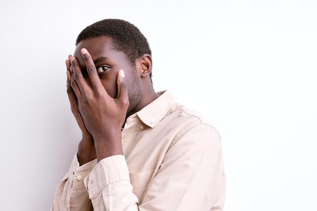 Geschokt afrikaanse man staan in angst, bang door iets, gezicht sluiten