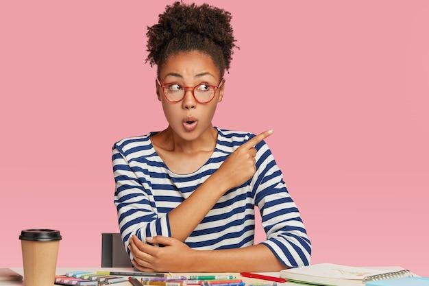 Geschokt afro-amerikaanse vrouw denkt over het maken van blauwdrukken, maakt illustratie met kleurpotloden