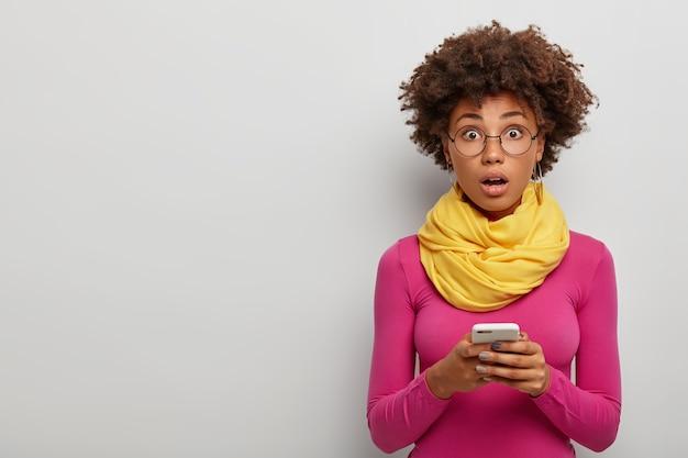 Geschokt afro-vrouw opent mond, staat sprakeloos binnen, gebruikt mobiele telefoon om te chatten in sociale netwerken