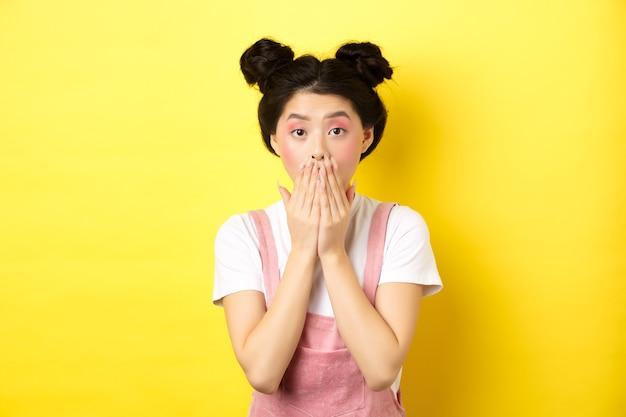 Geschokt aziatisch meisje hijgend verbaasd, starend naar iets schokkends, mond bedekt met handen, staande met schoonheidssmake-up en zomerkleding op geel.