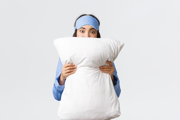 Geschokt aziatisch meisje in slaapmasker en pyjama staren vol ontzag, gezicht achter kussen verbergend terwijl ze horrorfilm kijken op logeerpartijtje, staande witte achtergrond geschrokken.
