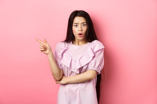 Geschokt aziatisch tienermeisje in jurk wijzende vinger naar links hijgend vroeg zich af en keek nieuwsgierig naar de camera terwijl...