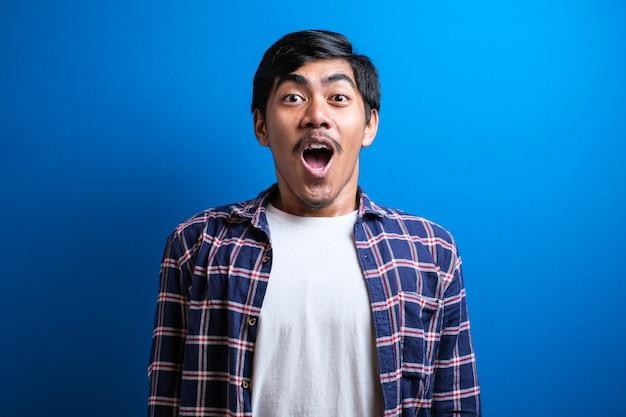 Geschokt aziatische man gekleed in casual ith open mond en handen omhoog kijkt naar de camera. verraste jonge aziatische studentenkerel op blauwe studioachtergrond