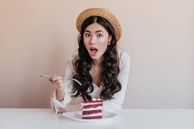 Geschokt aziatische vrouw die in hoed dessert eet. verbaasde chinese vrouw die van cake geniet.
