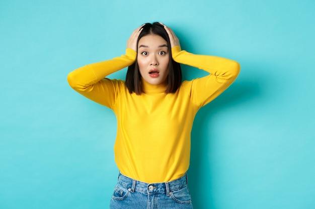 Geschokt aziatische vrouw kijkt sprakeloos, hijgend verbaasd en hand in hand op het hoofd, hoort groot nieuws, staande over blauwe achtergrond.