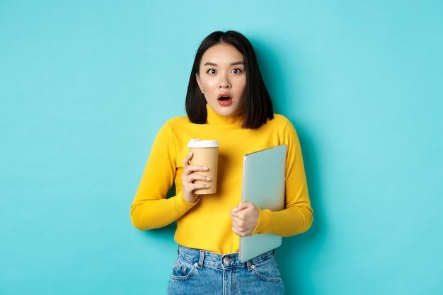 Geschokt aziatische vrouw werknemer, koffie drinken uit café afhaalmaaltijden, laptop vasthouden, hijgen en staren verbaasd naar de camera, staande over blauwe achtergrond