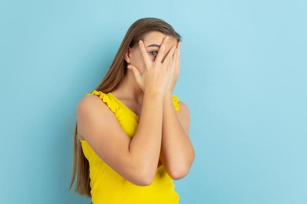 Geschokt, bang. het portret van het kaukasische tienermeisje dat op blauw wordt geïsoleerd
