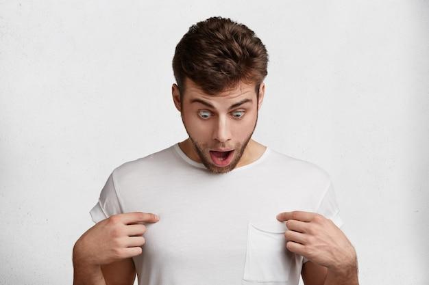 Geschokt bebaarde knappe man draagt casual t-shirt, geeft aan op lege kopie ruimte, staart met onverwachte uitdrukking, geïsoleerd op witte achtergrond. mensen, emoties en verrassingsconcept