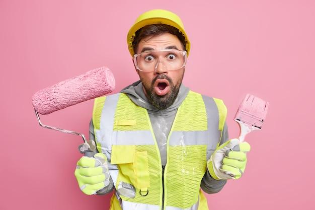Geschokt bebaarde reparateur houdt bouwapparatuur verft muren gekleed in bouwhelm reflecterende jas veiligheidsbril als professionele werknemer poseert binnen