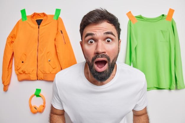 Geschokt beschaamde volwassen man met baard staart naar voren houdt mond wijd open van verbazing kan niet geloven in schokkend nieuws poseert binnenshuis met kledingstukken die aan de muur in de muur zijn gepleisterd