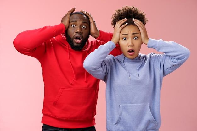 Geschokt bezorgd afro-amerikaans stel man vrouw hand in hand hoofd in paniek verwijd ogen verbijsterd ontvang slecht nieuws voel onrustig nerveus, staande roze achtergrond angstig