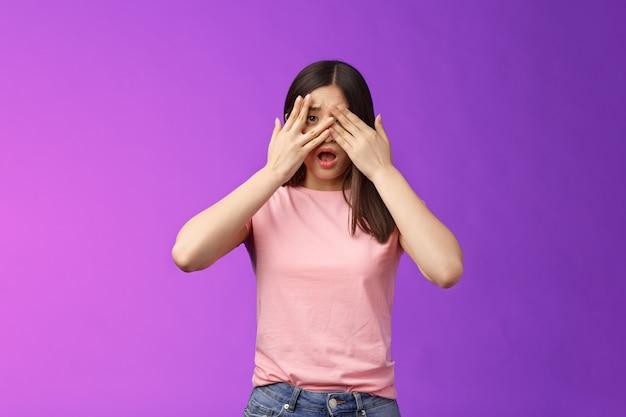 Geschokt bezorgd aziatisch meisje getuige van vreselijke misdaad voel me onzeker bang, sluit de ogen bang schudde, open mond, hijgend van streek, staande verdoving laat de kaak vallen, pose paarse achtergrond