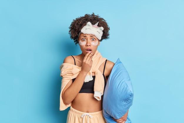 Geschokt bezorgd mooie afro-amerikaanse vrouw met krullend haar staart verbijsterd bang zijn voor iets gekleed in comfortabele pyjama houdt kussen geïsoleerd over blauwe muur