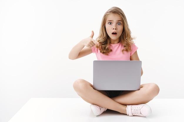 Geschokt bezorgd schattig blond meisje dochtertje laat moeder enge videocomputer zien, zit gekruiste benen, houd laptop vast, wijzend gadgetscherm, hijgend bang en nerveus, staar naar voren overstuur, witte muur