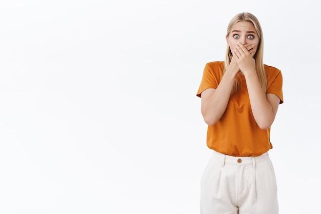 Geschokt bezorgde en bange jonge blonde vrouw met tatoeages, hijgende bedekkende mond met handpalmen en staren camera bang, freak-out van verbluffend nieuws, staande witte achtergrond