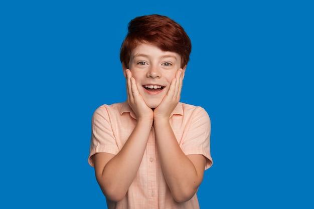Geschokt blanke jongen raakt zijn gezicht terwijl en glimlacht op een blauwe muur