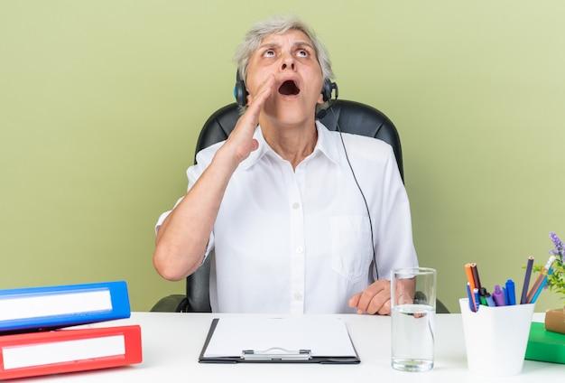 Geschokt blanke vrouwelijke callcenter-operator op koptelefoon zittend aan een bureau met kantoorhulpmiddelen met de hand dicht bij haar mond omhoog kijkend
