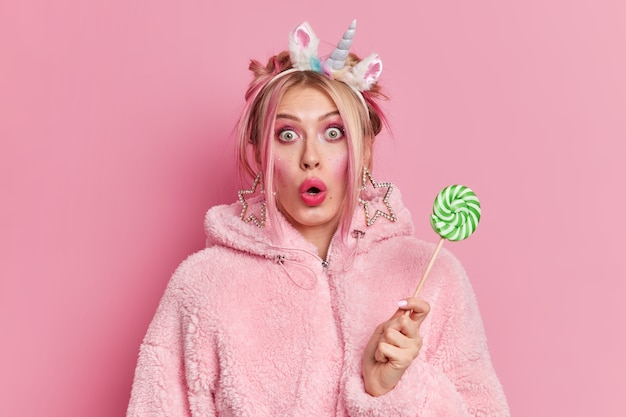 Geschokt blonde jonge vrouw staart camera afgeluisterd ogen heeft lichte make-up houdt groen snoep