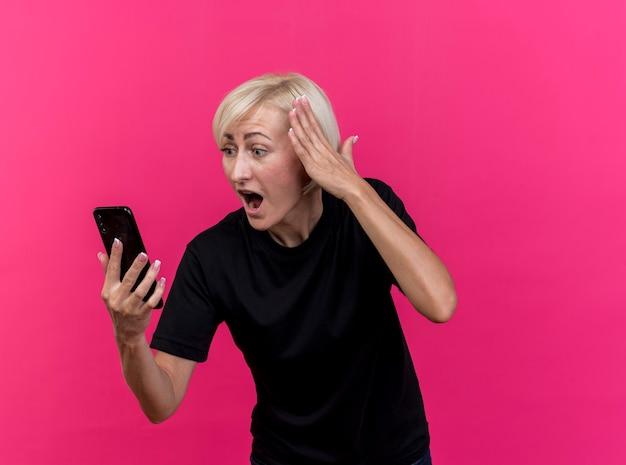 Geschokt blonde slavische vrouw van middelbare leeftijd houden en kijken naar mobiele telefoon aanraken van hoofd geïsoleerd op karmozijnrode muur met kopie ruimte