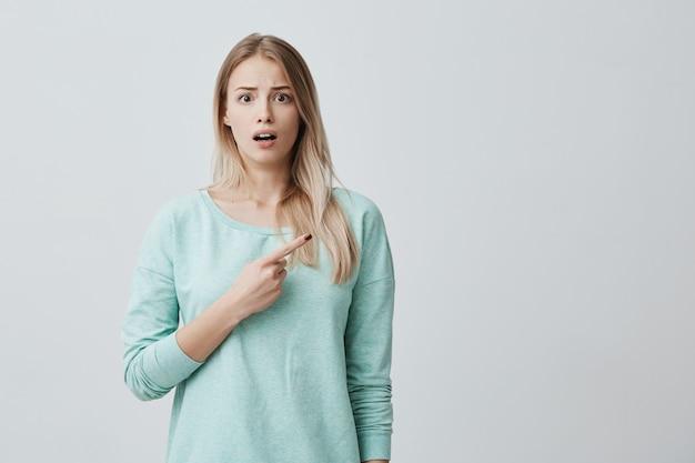 Geschokt blonde vrouw in blauwe trui met geopende mond fronsen gezicht kijken