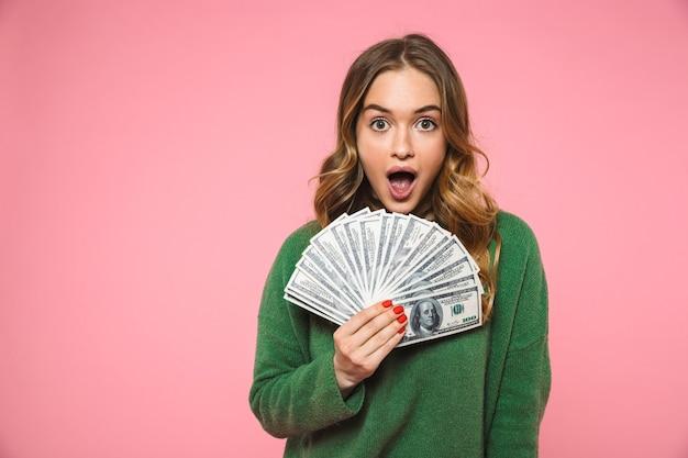 Geschokt blonde vrouw in groene trui met bankbiljetten en kijkend naar de voorkant met open mond over roze muur