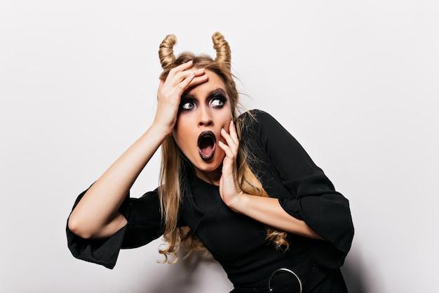 Geschokt blonde vrouw in halloween kostuum staan. bang heks poseren op witte muur.