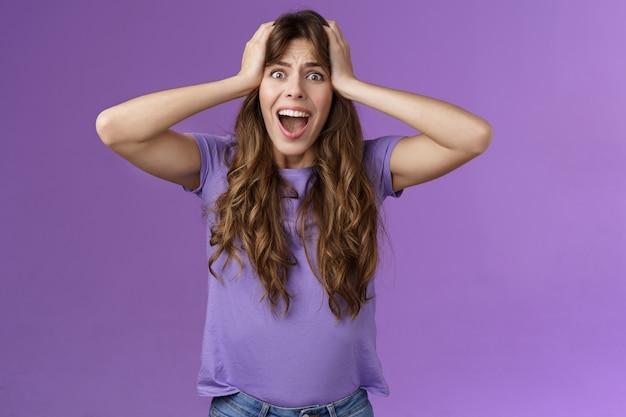Geschokt boos teleurgesteld krullend meisje schreeuwen verdriet gezicht lastige schokkende situatie grijp hoofd schreeuw paniek verontwaardigd boos en boos, staande verontruste paarse achtergrond