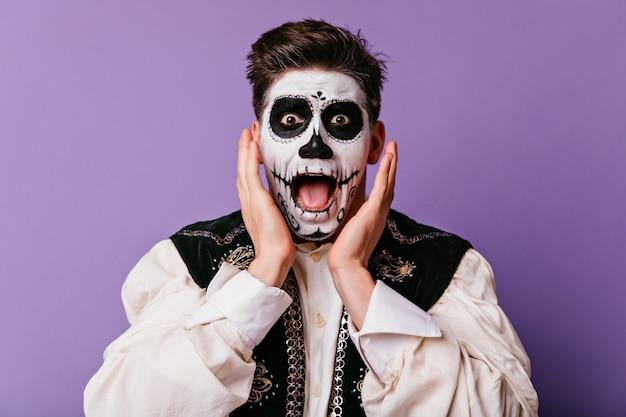 Geschokt bruinogige man schreeuwen op paarse muur. knap mannelijk model dat in zombiekostuum verbazing in halloween uitdrukt.