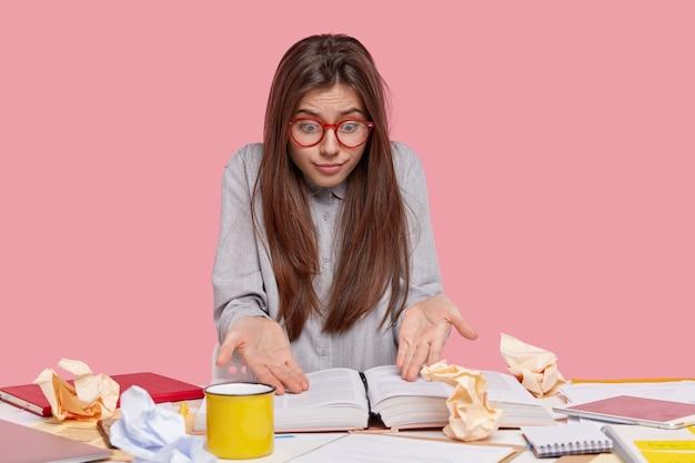 Geschokt brunette jonge vrouw draagt een optische bril, staart naar boek met verontwaardigde uitdrukking, gekleed in shirt, kan me geen informatie herinneren