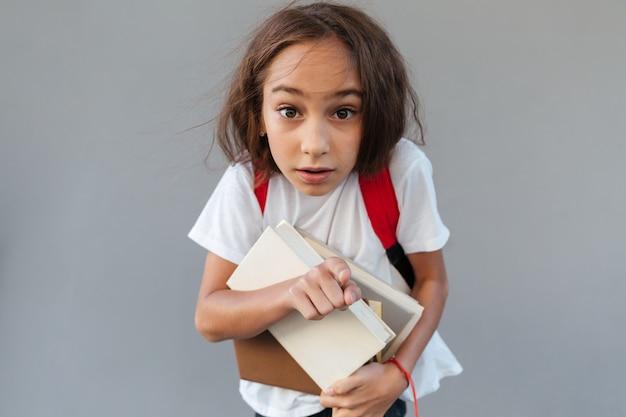 Geschokt brunette schoolmeisje met lang haar knuffelen boeken
