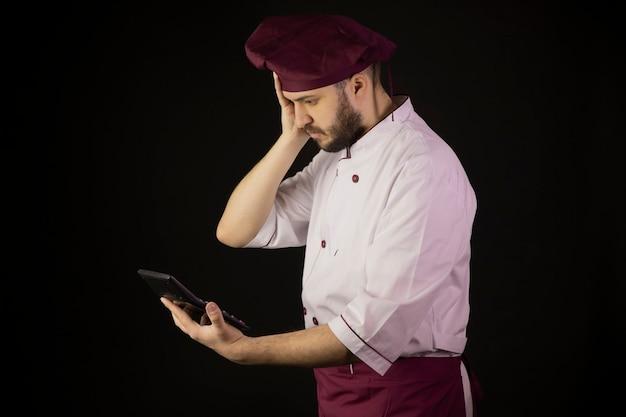 Geschokt chef-kok in uniform houdt rekenmachine vast en kijkt er verbaasd naar