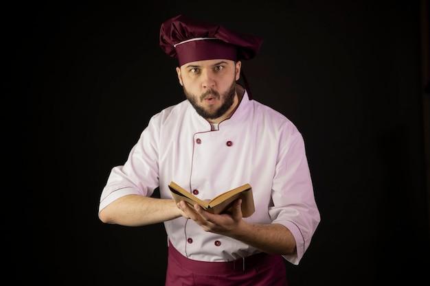 Geschokt chef-kok man in uniform houdt kookboek