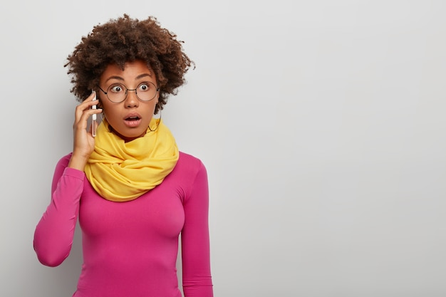 Geschokt dame met krullend haar belt collega, gebruikt moderne mobiele telefoons, concentreert zich op het verkrijgen van informatie tijdens telefoongesprekken, draagt een bril