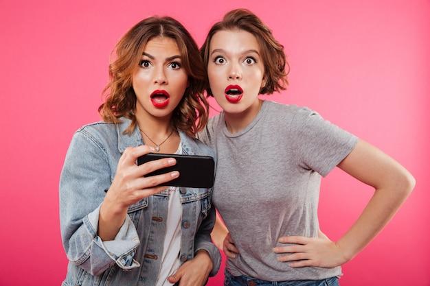 Geschokt dames vrienden met behulp van de mobiele telefoon.