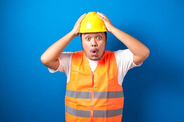 Geschokt dikke aziatische bouwvakker man houdt zijn handen op zijn hoofd met wijd open mond geïsoleerd.